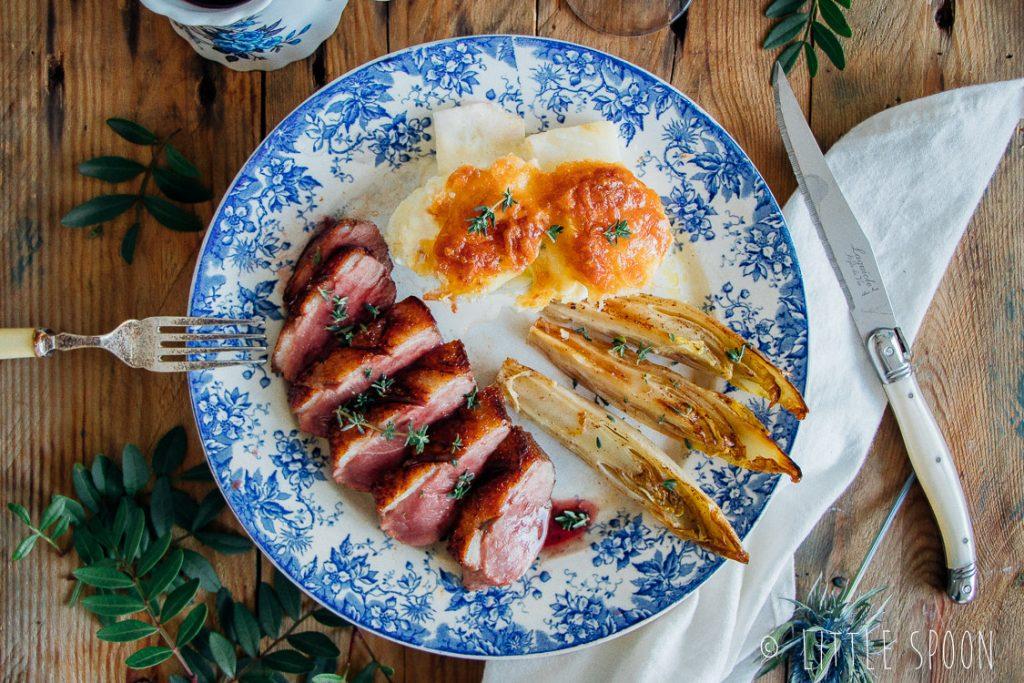 Op het vel gebakken eendenborst met portsaus, gekarameliseerde witlof en gratin van aardappel en knolselderij