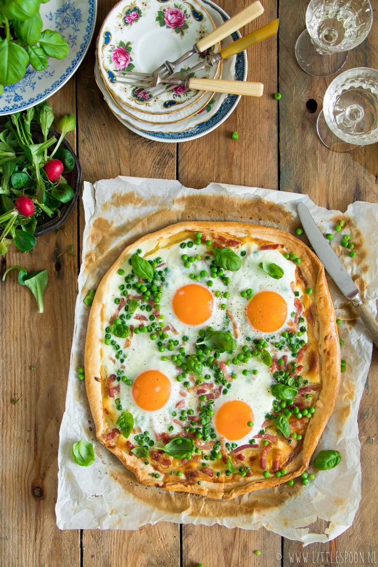 Verwarm de oven voor op 190 graden. Blancheer de erwtjes kort en spoel af onder de koude kraan. Leg het quichedeeg op een bakblik. Besmeer het deeg met de crème fraîche. Verdeel hierover de erwtjes en spekjes. Zet de flammkuchen 20 minuten in de oven. Haal eruit, breek de eitjes erop en breng op smaak met peper en zout. Zet nog eens 15 minuten in de oven Garneer met basilicum en snijd in punten.