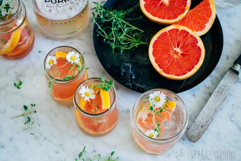 Alcoholvrije cocktail met sparkling water, rozensiroop, grapefruit en tijm