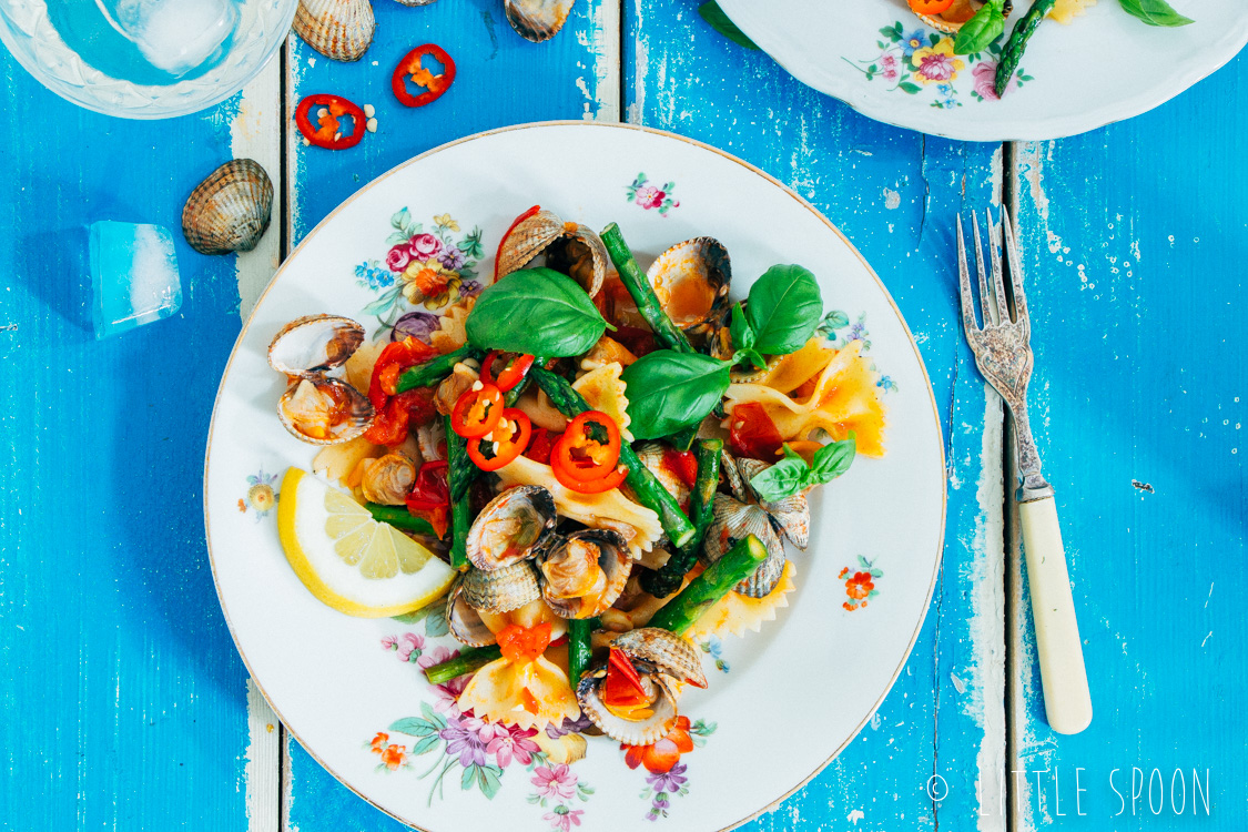 Lauwwarme pittige pastasalade met kokkels, groene asperges, tomaten en rode peper